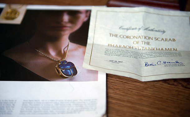 A photo of a booklet with a woman in a picture wearing a Scarab with blue stones.