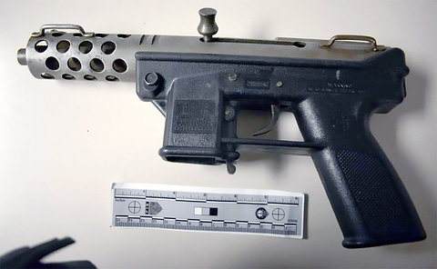Photo of a firearm with a size ruler below it