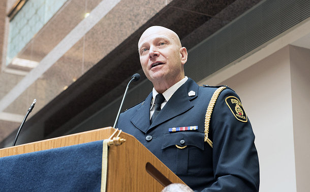 Man in a police uniform standing at a podium, speaking