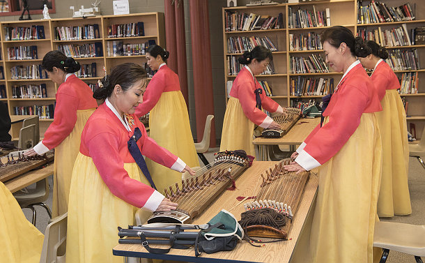 A group of women in traditional dress play string tabletop instrument