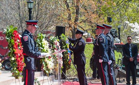 a man in uniform layng a wreath as three other men in uniform watch.