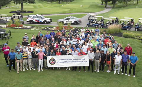 A large group on a golf course holding a banner