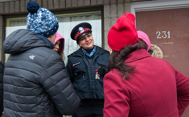 A woman in auxiliary uniform smiling and speaking to people