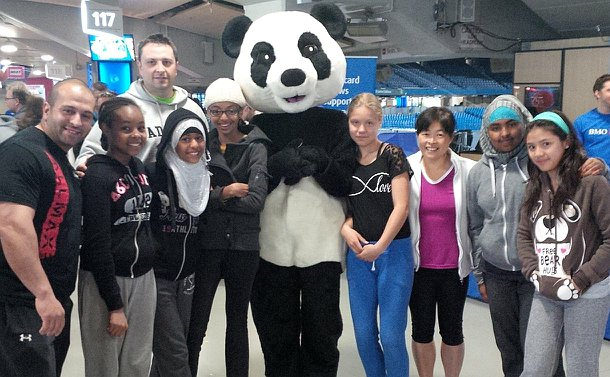 Two men and a group of girls with a Panda mascot