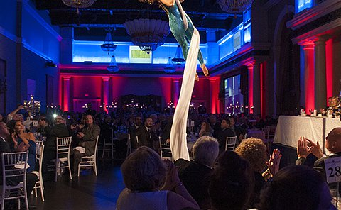 A woman suspended from the ceiling on fabric in a banquet hall