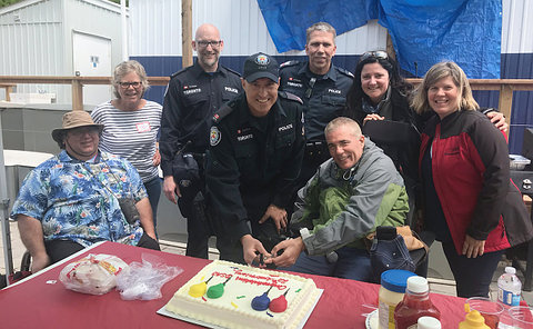 A group of people around a table with a cake