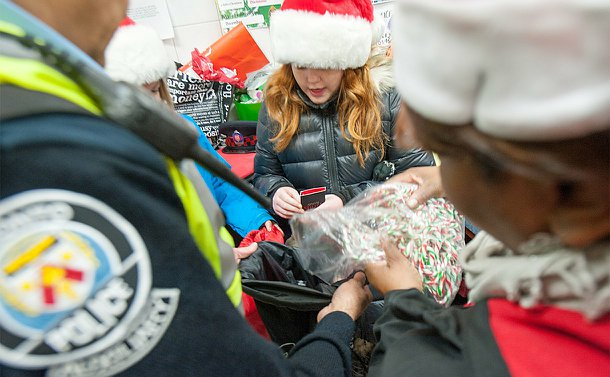 Three people sharing a bag of candy canes amongst two other bags
