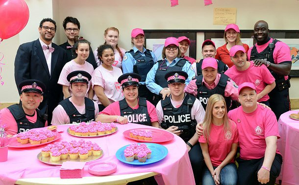 Group of men and women wearing various pink items of clothing sitting behind a table with pink cupcakes