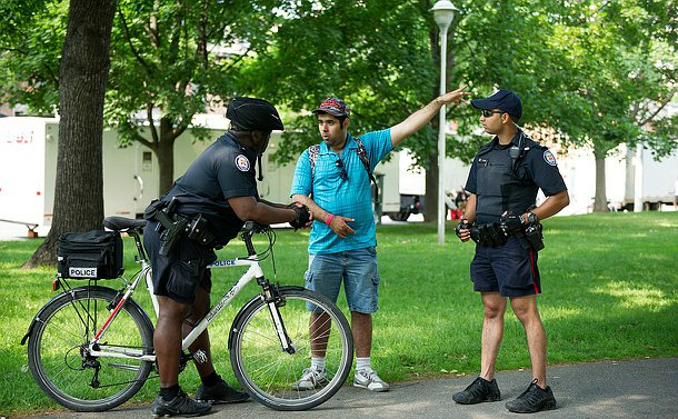 Two men in police uniform, one on a bicycle, listen to a man who is pointing in one direction