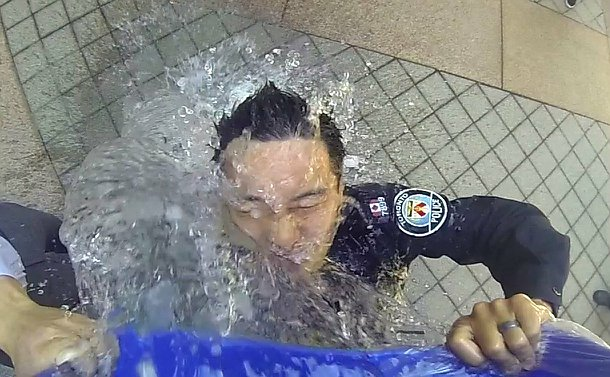 Photo looking downwards of a man in TPS uniform pouring water over his head