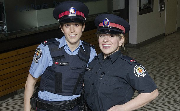 One woman in TPS auxiliary uniform with a woman in TPS uniform