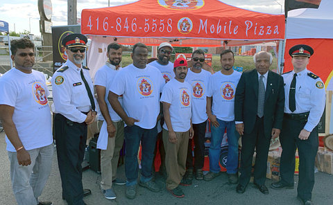 Two men in TPS uniform with men in matching T-Shirts