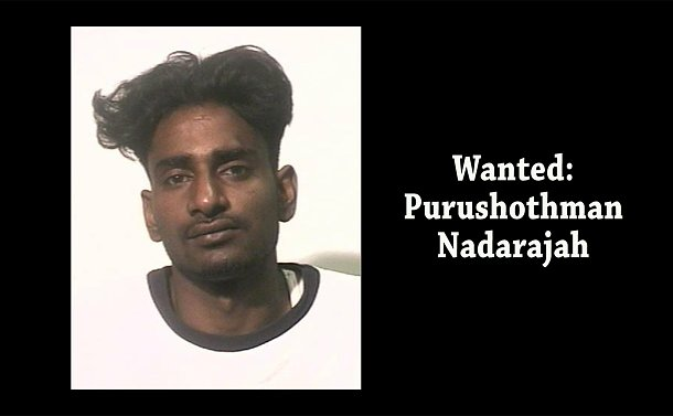 A close up of a man with the words Wanted: Purushothman Nadarajah
