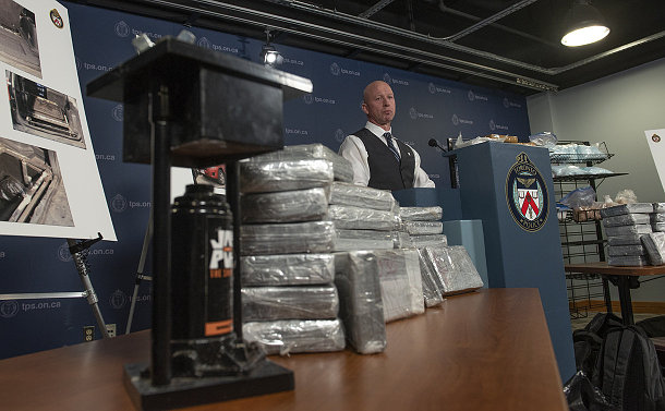 A man at a podium with a metal object and plastic wrapped blocks on a table
