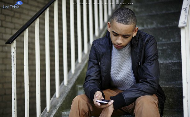 A boy seated on steps looking at a phone
