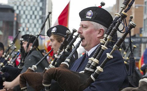 Close up of head and shoulders of four men playing bagpipes