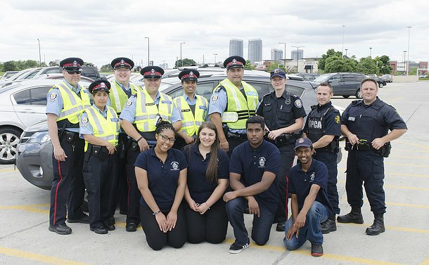 One woman in TPS uniform with men and women in TPS Auxiliary and OPSCA uniform and teenage boys and girls in TPS YIPI uniform
