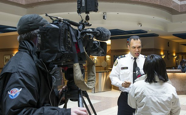 A man in TPS uniform speaks to a woman holding a microphone next to a TV camera