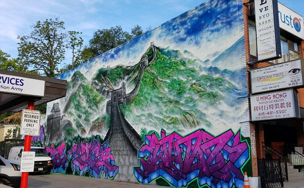 A wall with a mural near storefronts