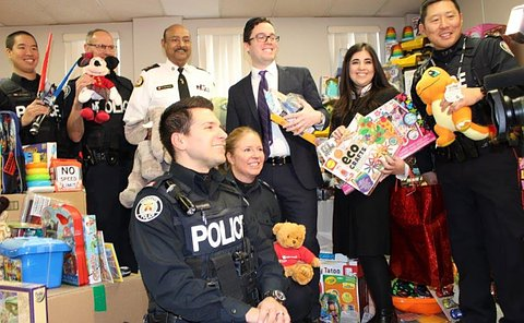 Men and women in TPS uniform holding toys