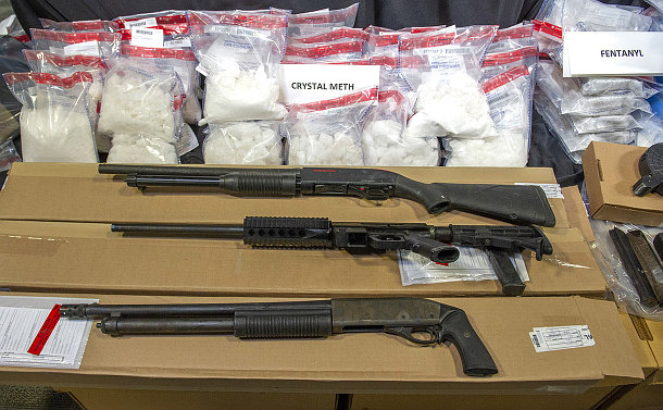 Three shotguns in front of packaged drugs