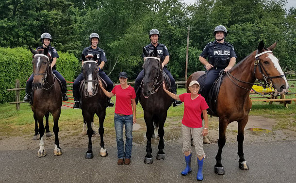 Four officers on horses with two people on the ground holding the horses