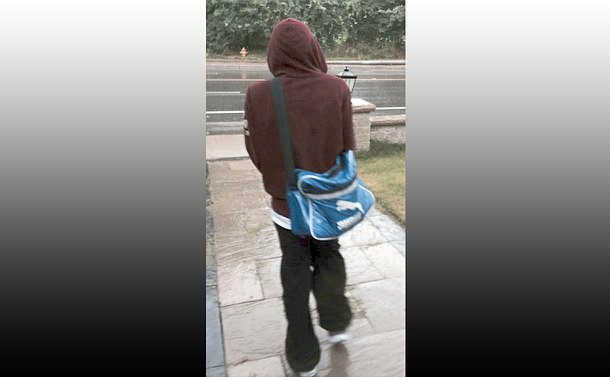 A person in a hooded sweatshirt walking away