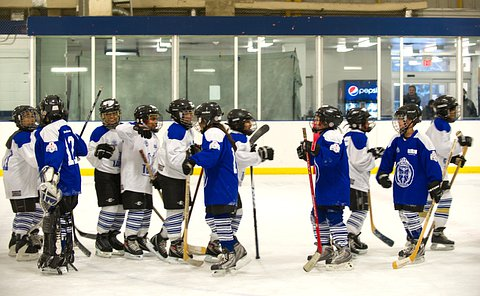 Two teams of children in hockey uniform shake hands at centre ice