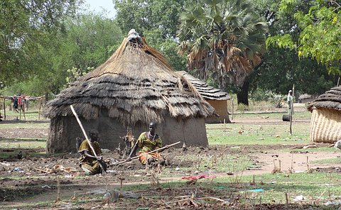 Two women kneeling with large sticks outside of a grass hut