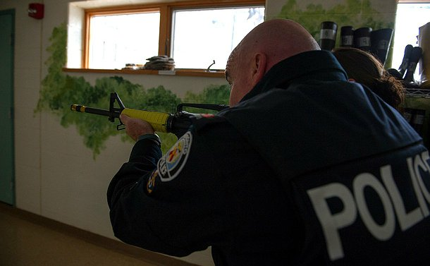An officer with a replica rifle aimed in front walking down a hallway of a school.
