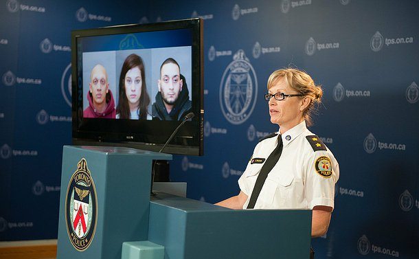 A woman in TPS uniform stands at a podium beside a television with three pictures of people on it