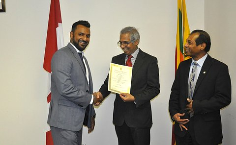 A man hands a certificate to another man as another man stands nearby