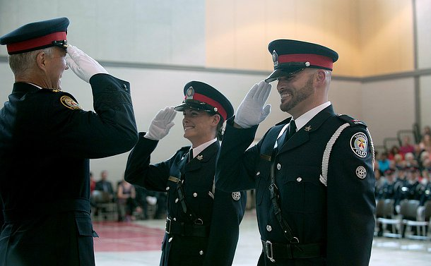 A man and a woman in TPS uniform stand smiling and saluting another man in TPS uniform