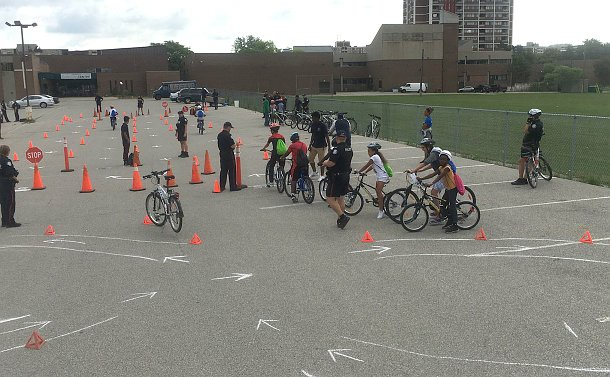 A parking lot with cones and chalk marks outlining a course where people in TPS uniform stand and children on bicycles ride
