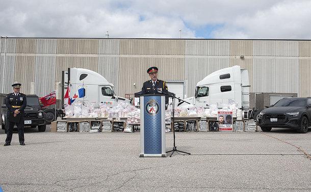 A man in TPS uniform in front of tables of bundled drugs and semi-trucks