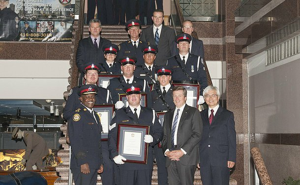 A group of men and women in TPS uniform on a staircase along with others in business suits
