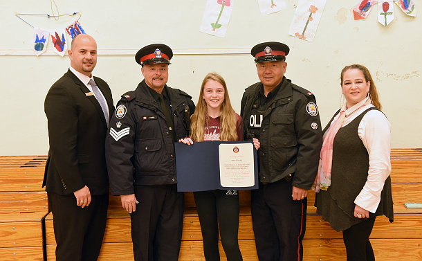 Two men in TPS uniform with a girl holding a certificate and standing beside a man and woman