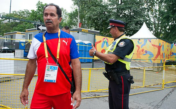 An officer in uniform giving a thumbs up to a Cuban Field Hockey player who is wearing his uniform.