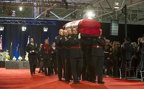 Eight men in uniform carry a casket draped in the Canadian flag on red carpet as people look on