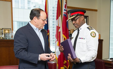 The chief looking at a photo album as a man stands next to him