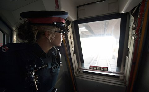 A female officer in uniform looks out from the front of a TTC train.