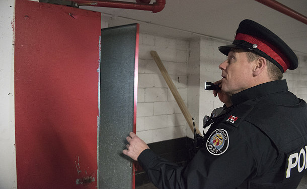 A man in TPS uniform opens a metal cabinet