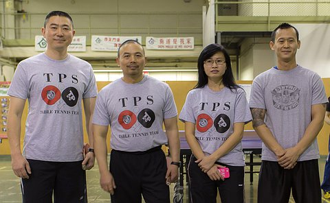 Three men and one woman stand in a line in grey TPS shirts in gym setting