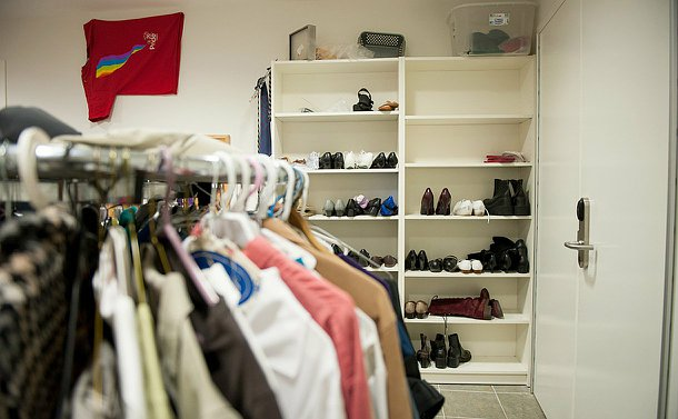 A clothing rack in left foreground and book shelves filled with shoes in right background