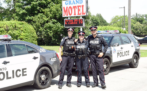 "Two women and one men stand in-front of a sign that reads ""Grand Motel"""
