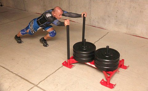 A man pushing a weighted sled