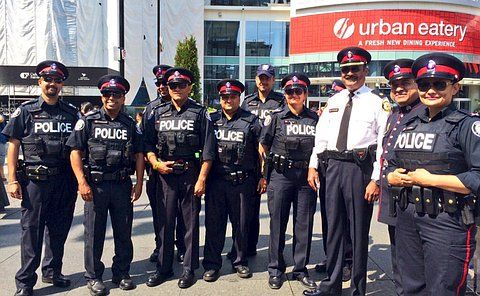 Officers in uniform posing for a photo, about a dozen officers.