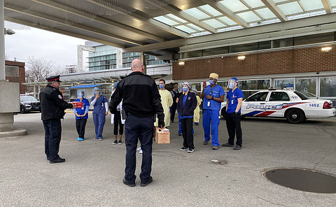 A group of people in hospital protective gowns and masks talking to men in TPS uniform