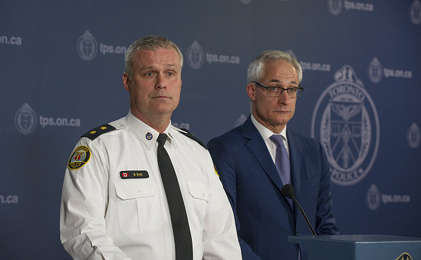 A man in TPS uniform and another man at a podium