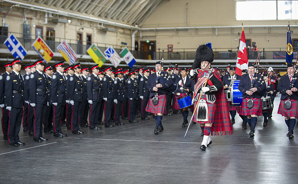 A line of officers in uniform with band marching